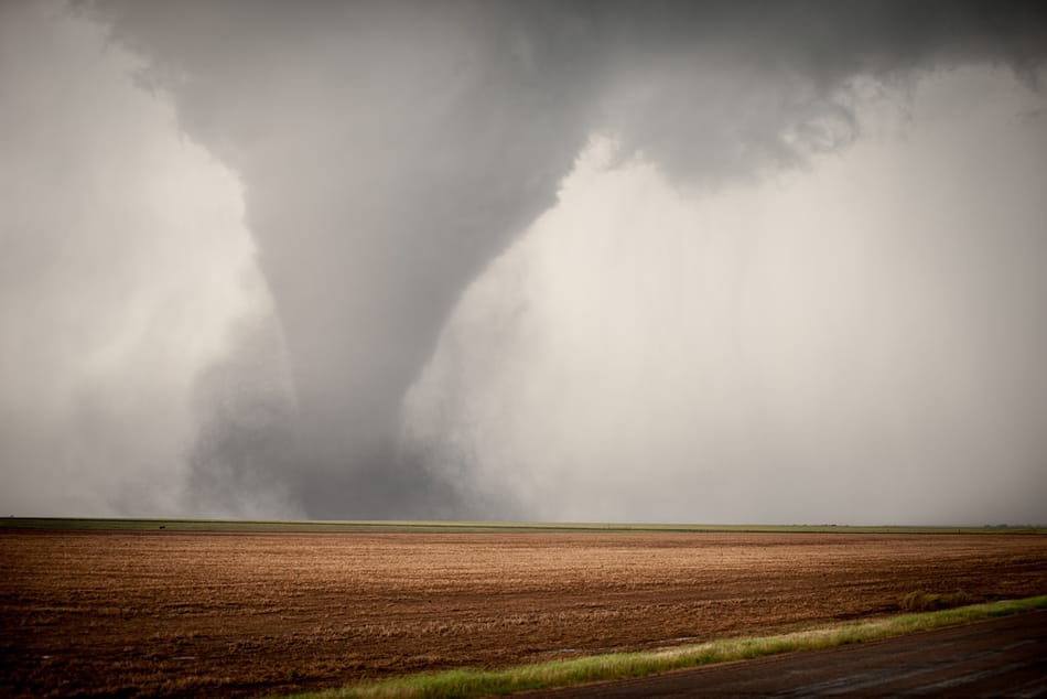 A tornado about to strike in an open field.