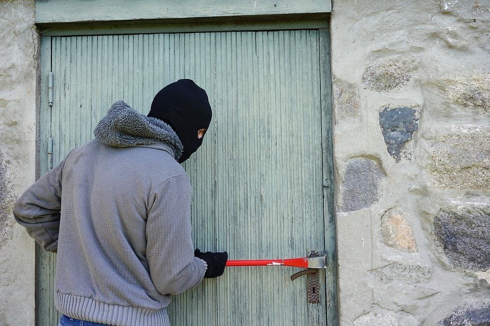 Burglar breaking into an unsecured home.
