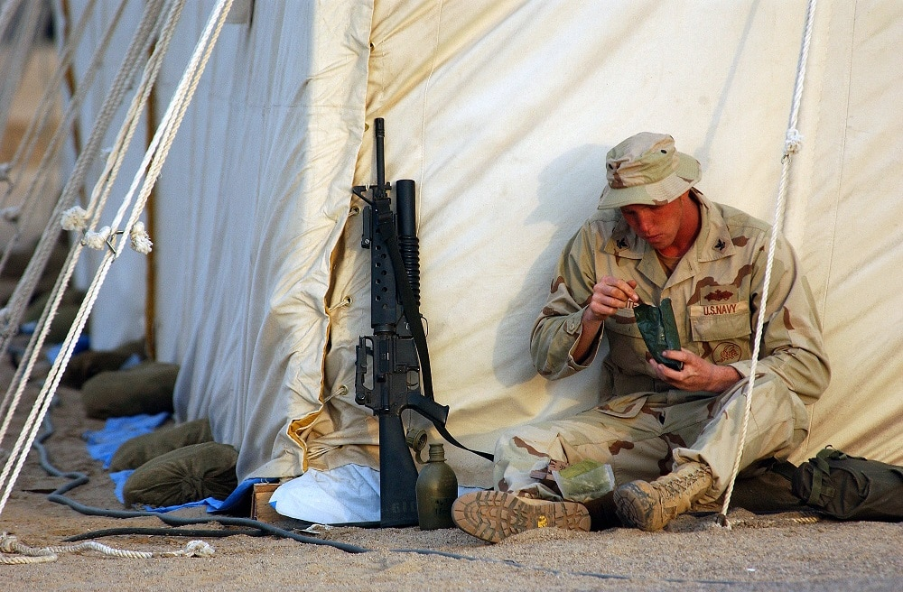 U.S. Navy service member eating an MRE while deployed.